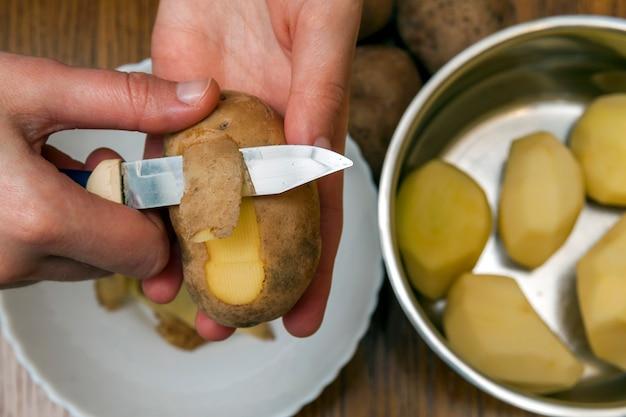 Détail des mains de femme éplucher une pomme de terre jaune fraîche avec un couteau de cuisine