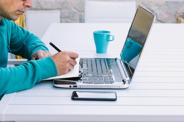 Détail des mains d'un homme qui écrit dans son cahier, télétravaillant avec son ordinateur portable, dans le jardin de sa maison