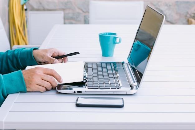 Détail des mains d'un homme qui lit son cahier, télétravaillant avec son ordinateur portable, dans le jardin de sa maison