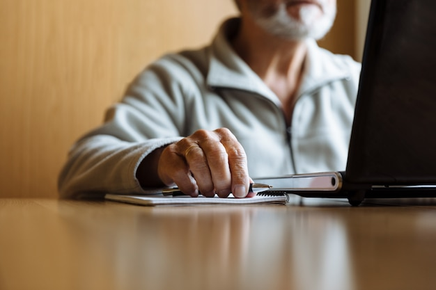 Détail des mains de l'homme senior travaillant sur l'ordinateur portable