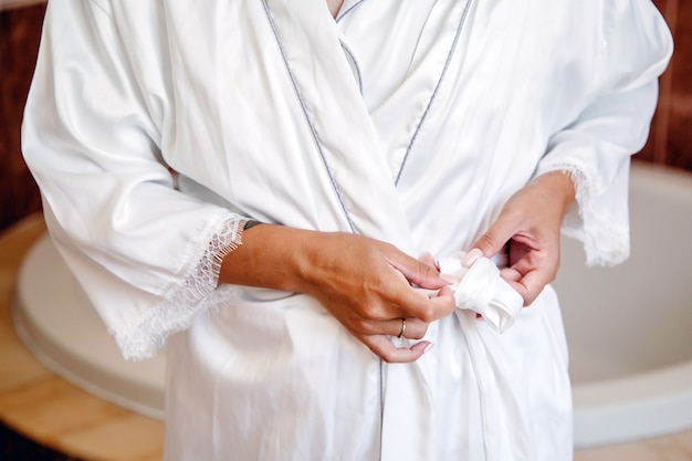 Détail des mains d'une mariée méconnaissable attachant la ceinture de sa robe de pyjama nuptiale