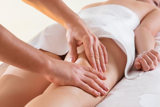 Détail des mains massant le muscle du mollet humain.