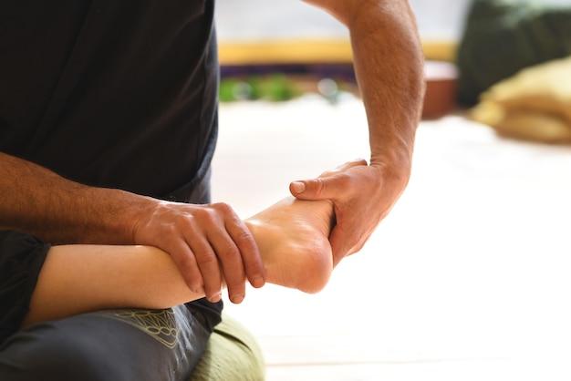 Détail des mains massant les pieds, réflexologie