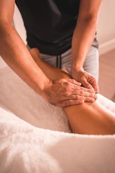Détail d'un massage du physiothérapeute à l'arrière de la jambe gauche d'une jeune femme allongée sur la table. physio, ostéopathie, massage relaxant, vidéo en mouvement du traitement sur le dos