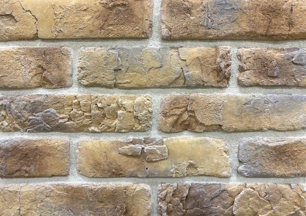 Détail d'un mur fait de carreaux décoratifs en pierre beige et coutures grises pour la décoration murale
