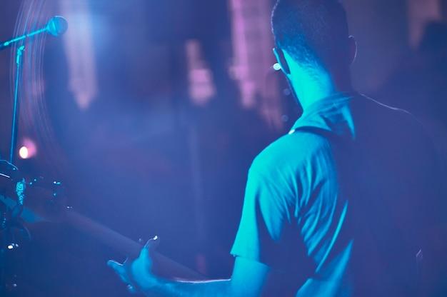 Détail d'un musicien de rock qui joue de la basse en direct lors d'un concert avec de la fumée et des lumières tamisées. photo artistique avec le plan filtré des lumières.