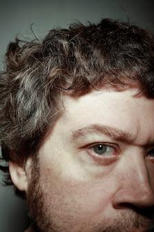Détail de l'œil bleu de l'homme avec des veines dans la région scrotale