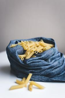 Détail des penne de pâtes dans un lin bleu
