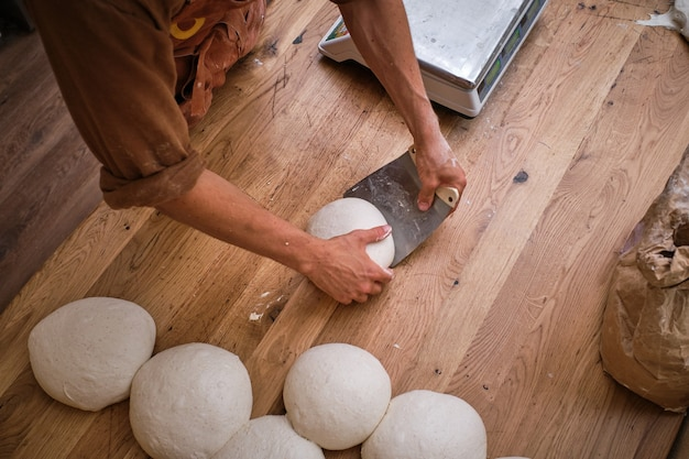 Détail de la photo des mains d'un boulanger travaillant la pâte à pain