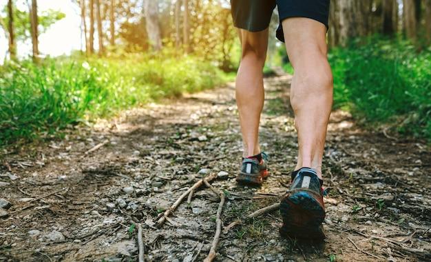 Détail de pieds de jeune homme participant à une course de trail à travers la forêt