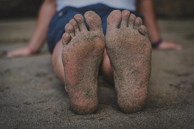 Détail des pieds de sable d'un homme adulte assis sur la plage détendue