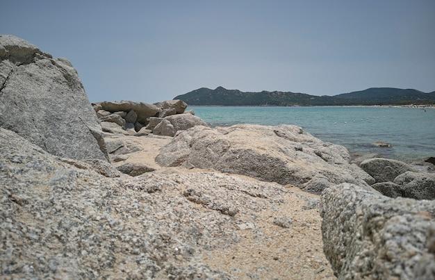 Détail de pierres et de rochers qui surplombent la mer cristalline ci-dessous.