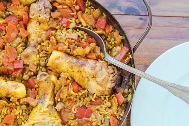 Détail d'une poêle à paella espagnole typique avec du riz au poulet et au safran ou paella au poulet, une louche pour servir à l'intérieur du riz et une assiette blanche. cuisine espagnole typique.