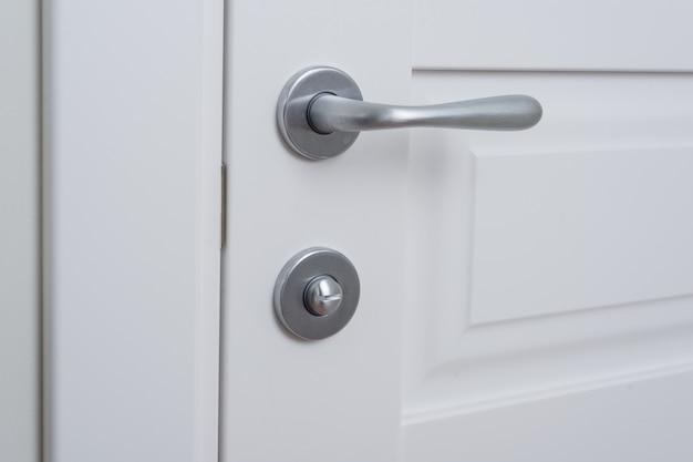 Détail d'une porte intérieure blanche avec une poignée de porte chromée