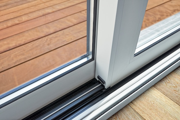 Détail de la porte en verre coulissant et rail encastré dans le sol