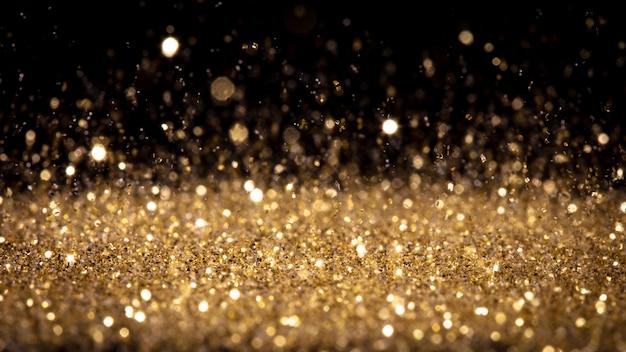 Détail de la poussière d'or scintillante en mouvement.