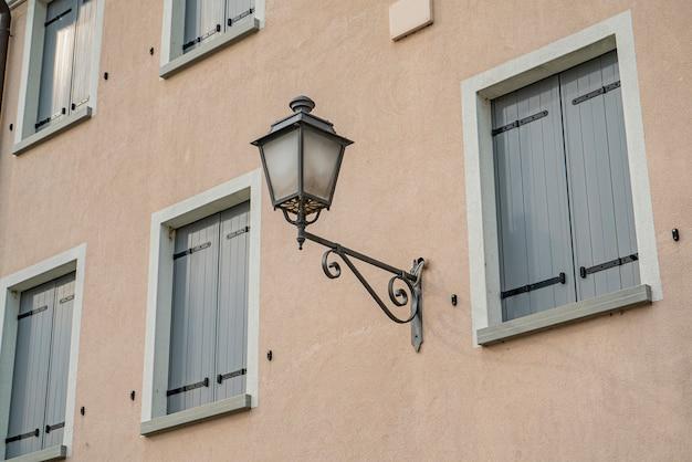 Détail d'un réverbère antique sur la façade du bâtiment aux couleurs froides