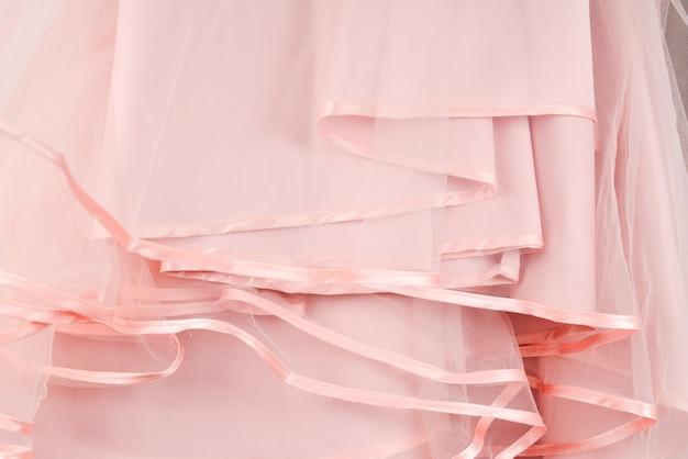 Détail de la robe de mariée. les volants de la robe de mariée rose se bouchent.