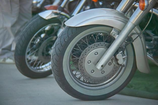 Détail d'une roue d'une moto vintage avec frein à disque bien visible et détails de la bande de roulement.