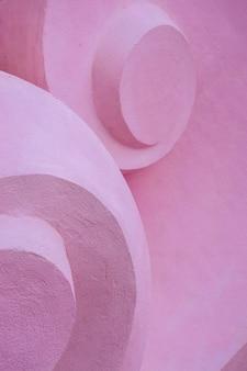 Détail de la sculpture en pierre de volume avec des formes tourbillonnantes. fond convexe en béton rose