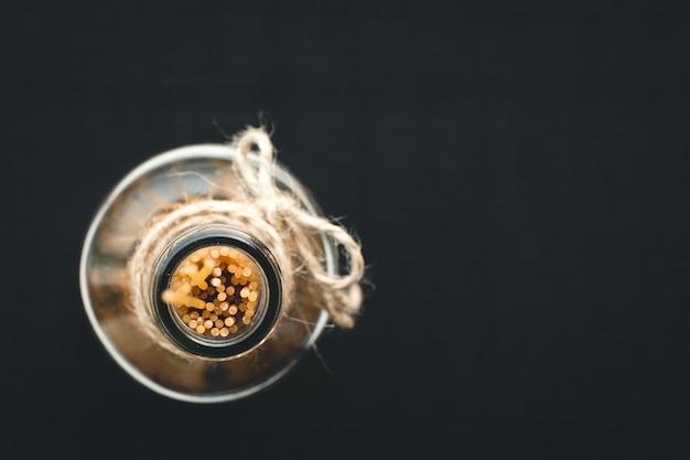 Détail de spaghetti de pâtes dans une bouteille de verre d'huile d'olive vide sur fond noir