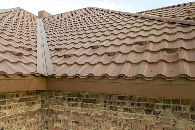Détail de la structure du toit de la maison recouverte de feuilles de tuiles métalliques brunes.