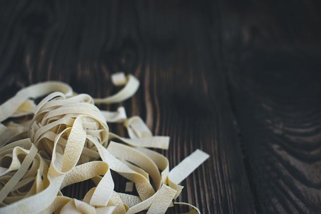 Détail des tagliatelles de pâtes sur un fond en bois