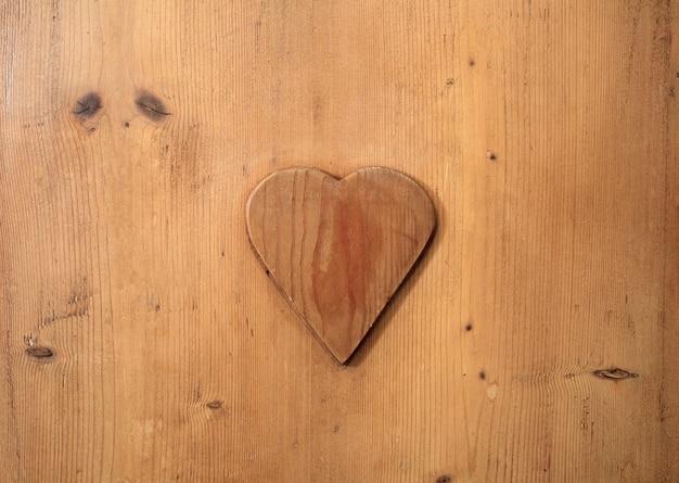 Détail d'une texture de fond en bois avec coeur incurvé dans une décoration en bois amour élégant design romantique couleurs naturelles