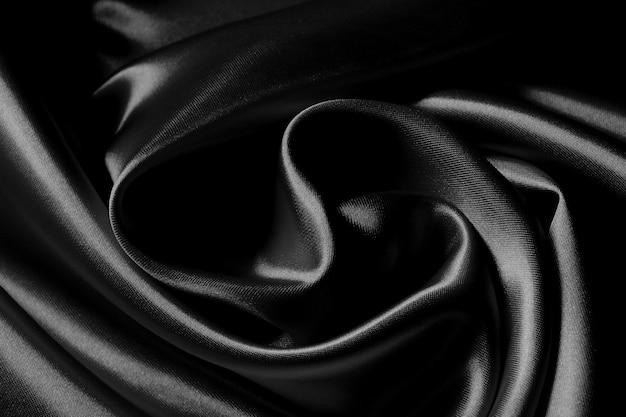 Détail d'une texture de tissu de soie ondulée noire.