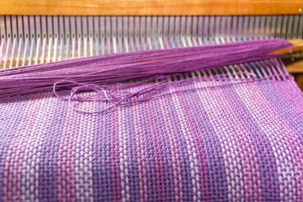 Détail de tissu dans le peigne à tisser avec des couleurs ultraviolettes et lilas