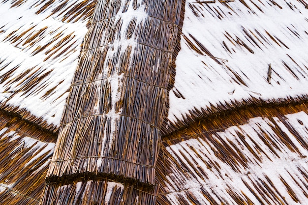 Détail de la toiture en paille avec de la neige