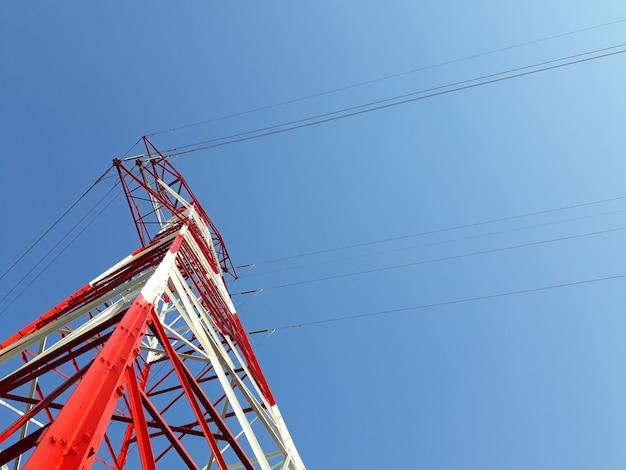 Détail des tours à haute tension peintes en rouge au sommet d'une montagne.
