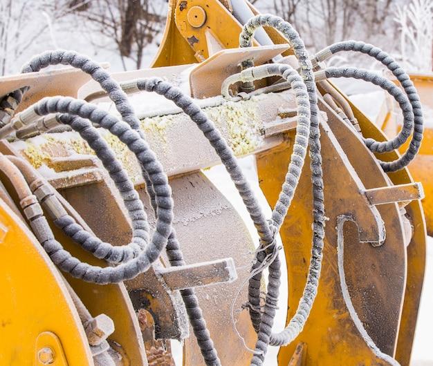 Détail des tuyaux avec la saleté et le givre d'une excavatrice