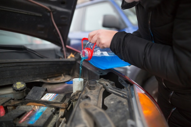 Détail sur verser le lave-glace liquide antigel dans la voiture sale du réservoir d'eau antigel bleu et rouge, concept de voiture