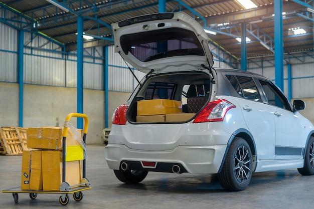 Détaillant chargeant une boîte en carton dans un coffre de voiture dans un entrepôt, distribution de colis, logistique, concept de livraison
