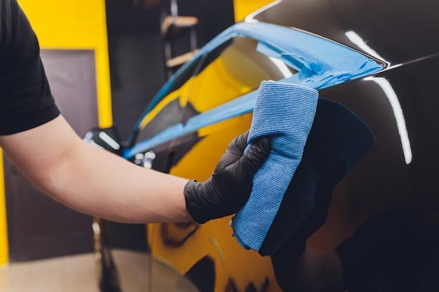 Détaillant de voiture - mains avec polisseuse orbitale dans un atelier de réparation automobile.