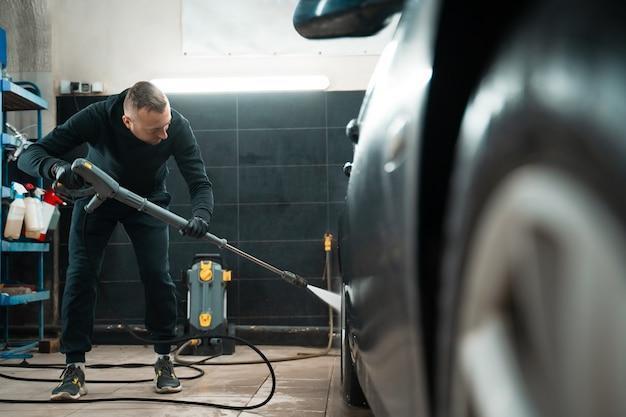 Détailler l'employé lave la voiture avec un nettoyeur haute pression