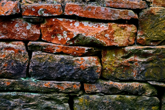 Détailler la texture du mur de pierre coloré avec du rouge et du lichen