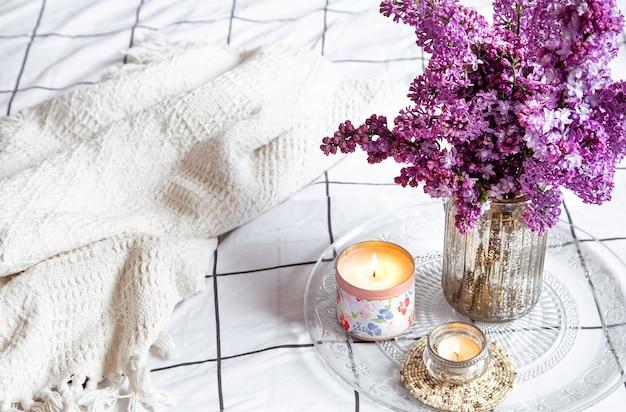 Détails de décoration cosy et bouquet de fleurs lilas fraîches sur une table lumineuse.