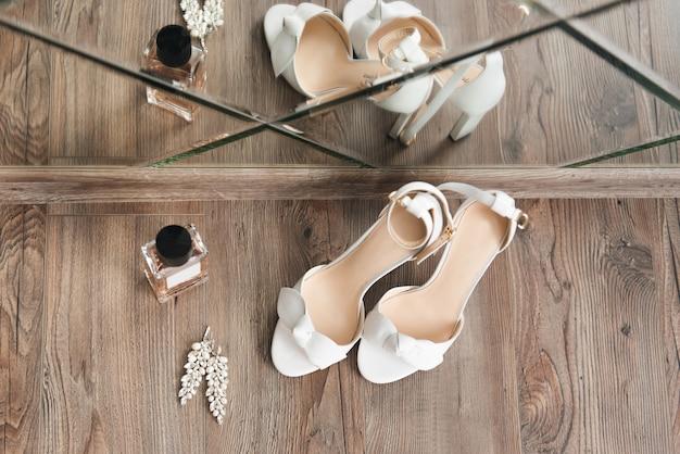 Les détails du jour du mariage. chaussures de mariée sur une vue de dessus de fond clair
