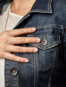 Détails du modèle portant une veste en jean bleu