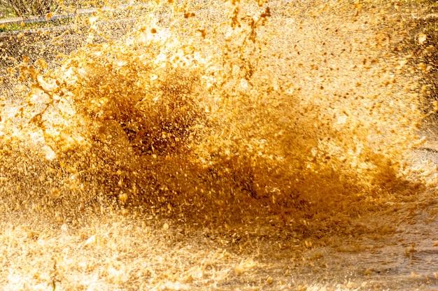 Détails des gouttes d'eau et de la boue d'une éclaboussure dans une flaque d'eau dans une course d'obstacles.