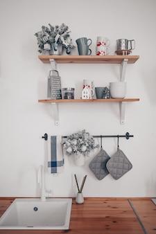 Détails de l'intérieur de la cuisine élégante blanche moderne avec des éléments en bois dans un appartement de style scandinave
