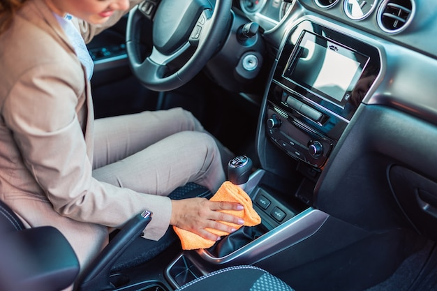 Détails de l'intérieur de la voiture. une femme d'affaires heureuse essuie et nettoie l'intérieur de sa voiture.