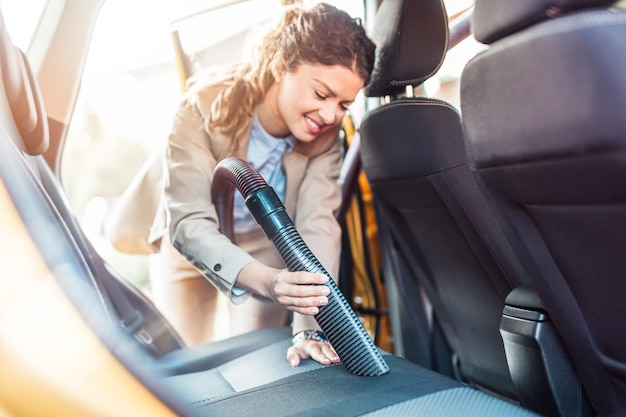 Détails de l'intérieur de la voiture. une femme d'affaires heureuse nettoie l'intérieur de sa voiture avec un aspirateur.