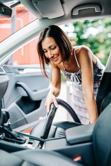Détails de l'intérieur de la voiture. une femme heureuse d'âge moyen nettoie l'intérieur de sa voiture avec un aspirateur.