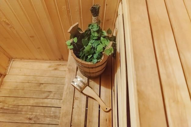 Détails intérieurs sauna finlandais bain de vapeur hammam avec accessoires de sauna traditionnel bassin bouleau balai scoop feutre chapeau serviette