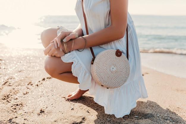 Détails de mode gros plan de femme en robe blanche avec sac à main en paille style été sur accessoires de plage