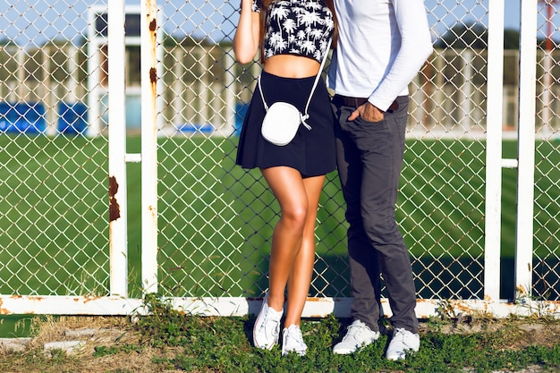 Détails de mode, jeune couple posant sur un terrain de sport, portant des vêtements décontractés et des baskets tendance hipster noir et blanc, journée ensoleillée, couleurs vives.