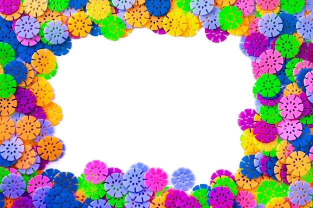 Détails multicolores en forme de flocons de neige du designer pour enfants sur fond blanc. disques en plastique pour le développement de la motricité fine des doigts.
